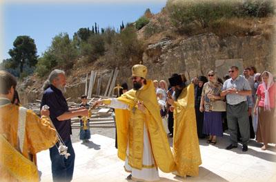 Архимандрит Елисей кропит святой водой верующих